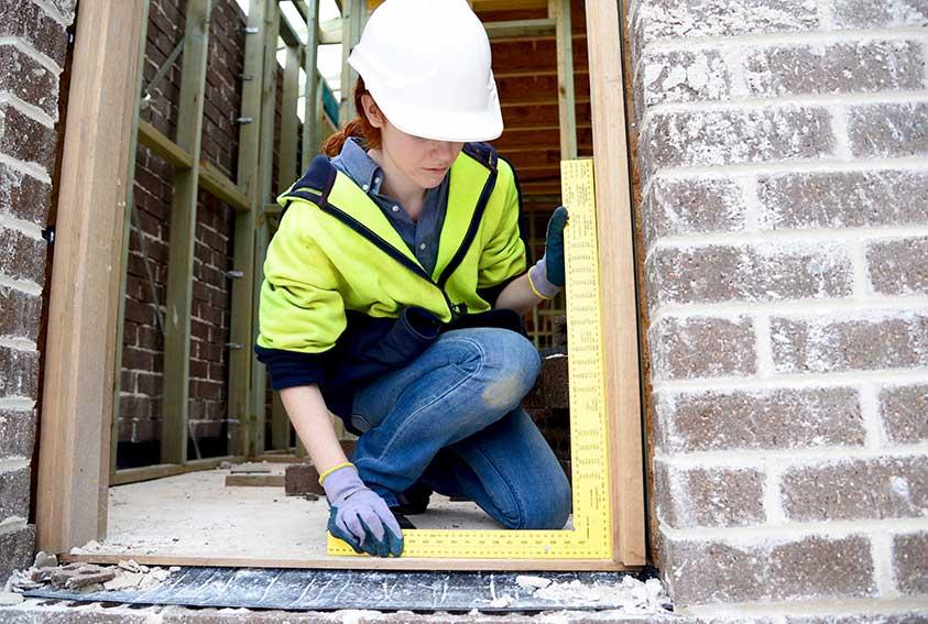 woman measuring door frame commercial door installation